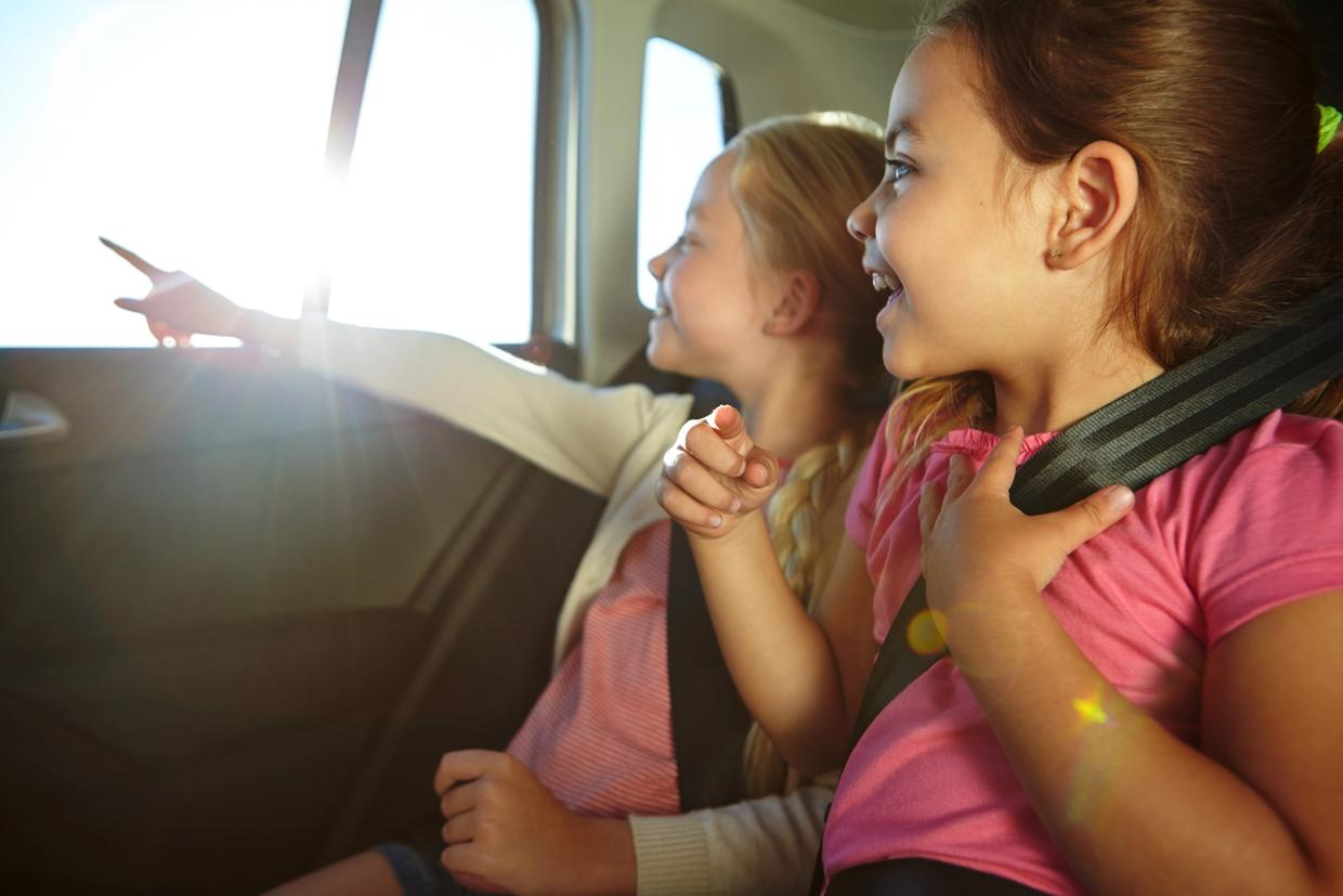Two girls looking out the car window