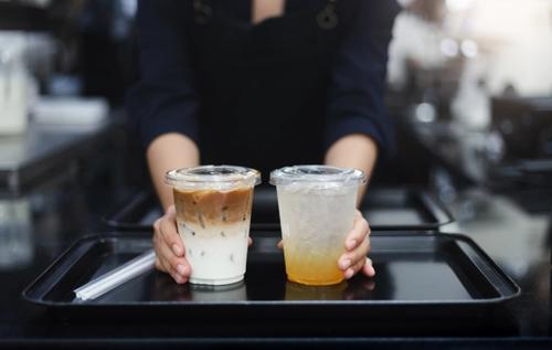 Two plastic cups on a tray held by a barista