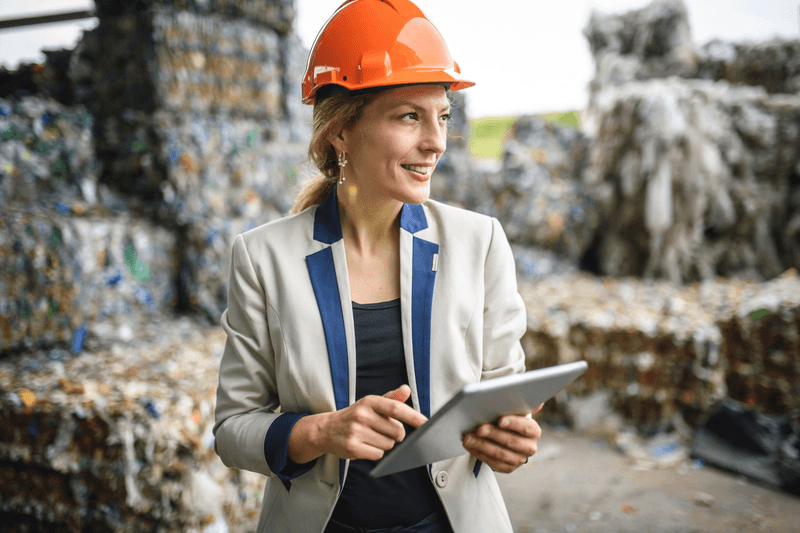 Woman in a hard hat in front of recycled plastic