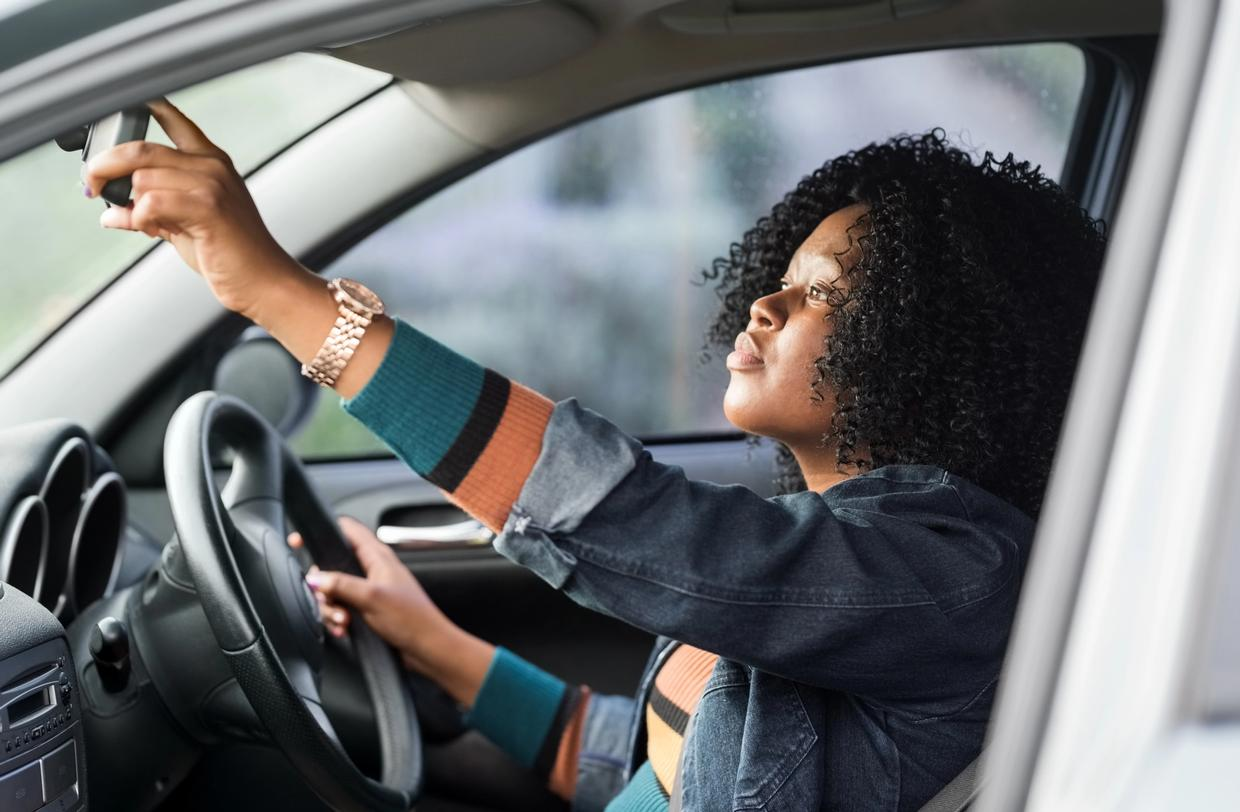 Women looking through front rear view mirror