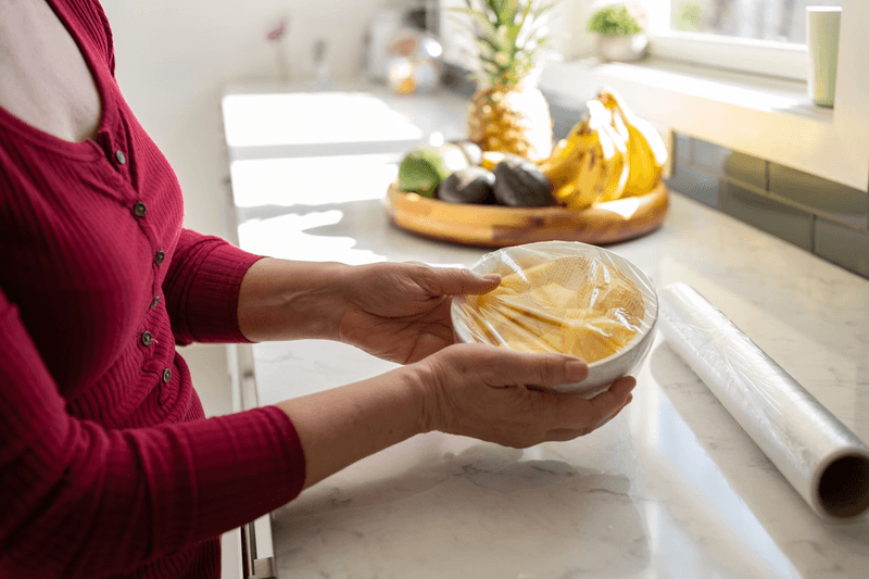 Woman wraps bowl of food with plastic cling wrap