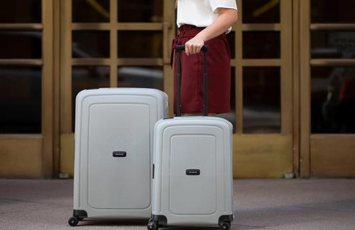 person walking with rolling suitcases