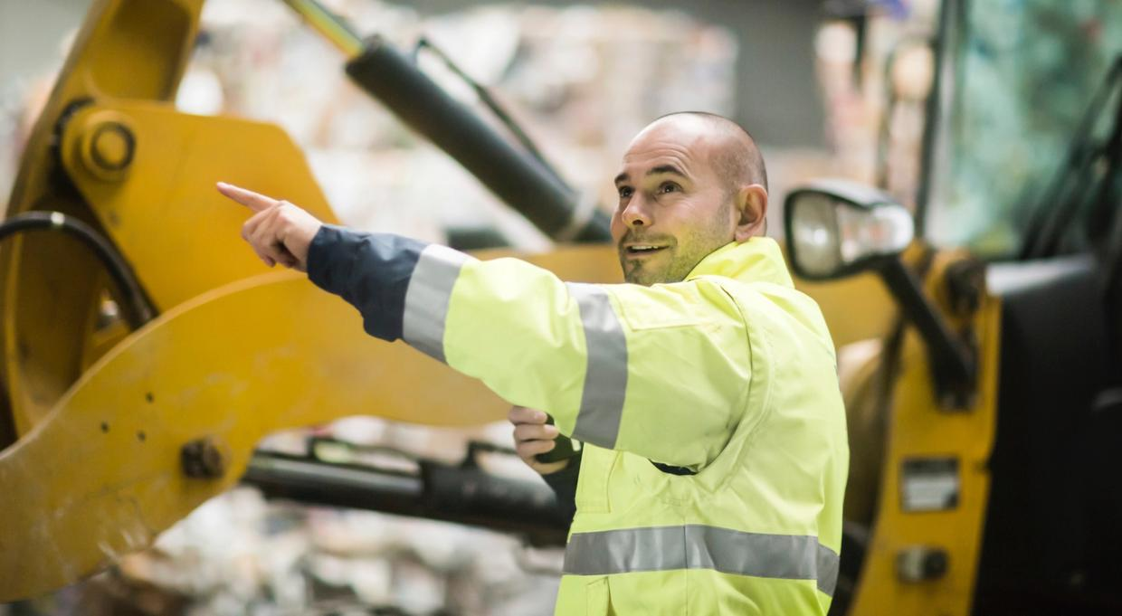 Worker directing machinery at a recycling plant