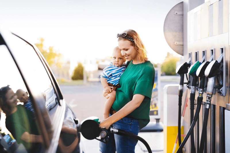 Woman pumping gas with baby