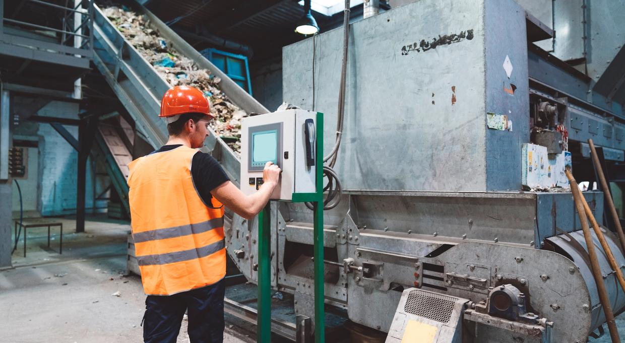 Worker using computer at recycling facility