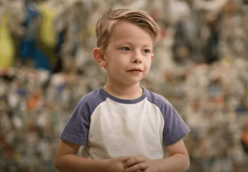 Kid sitting in front of recyclable plastic