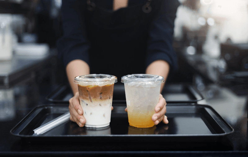 Barista holding two plastic cups on a tray