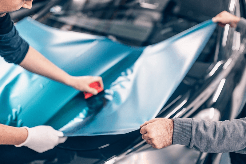 Two auto manufacturing employees applying vinyl plastic to a vehicle