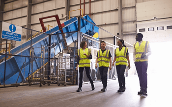A group of people in yellow safety vests walking through a warehouse